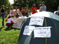 One of the many tents covered in statements on climate change is flanked by DivestNU protestors.
